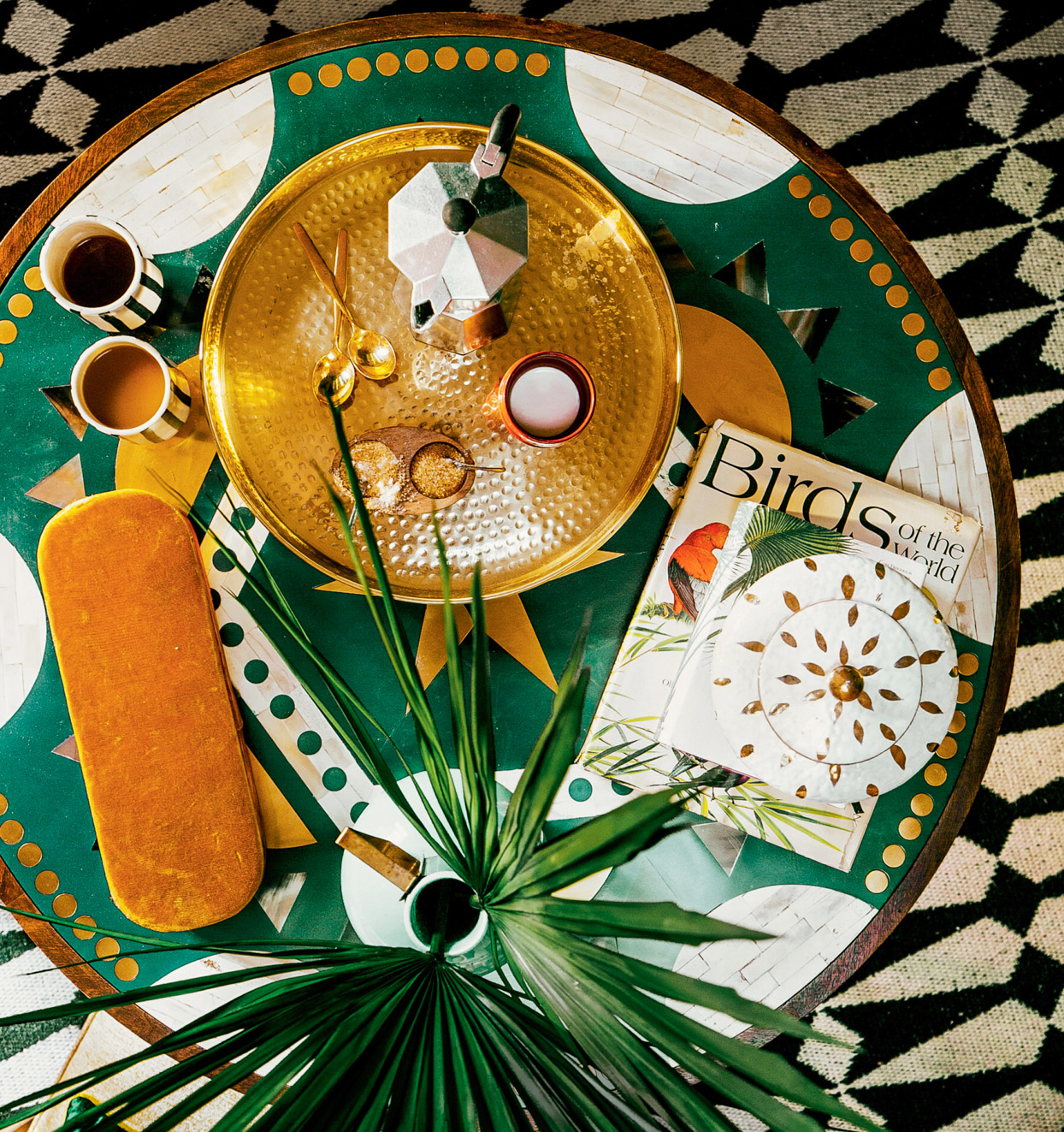 patterned table with golden tray and plant