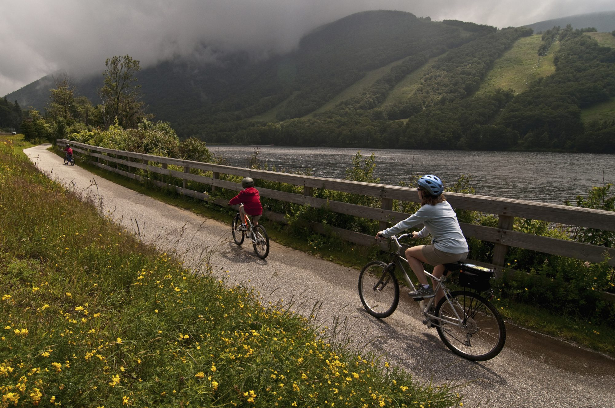 woman riding bikes with children on path along echo lake