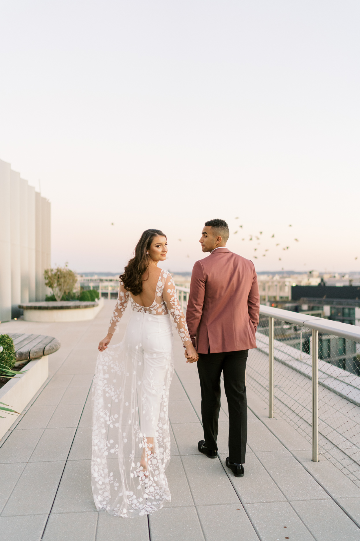 bride and groom hold hands looking back on building terrace
