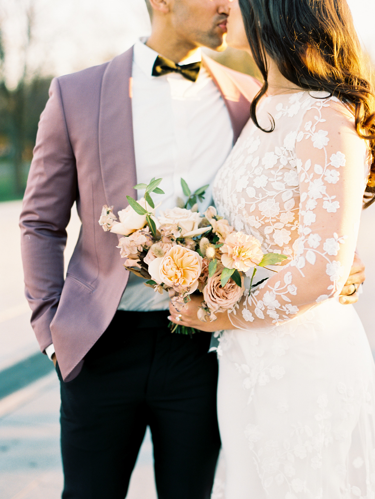 bride and groom kiss while bride holds blush toned floral wedding bouquet