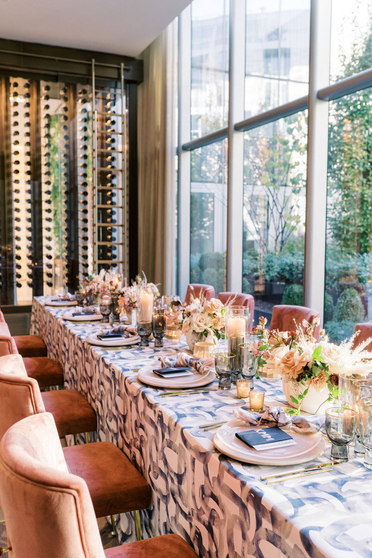 long wedding reception table with orange chairs