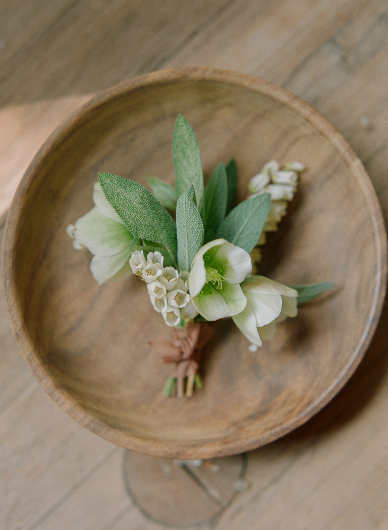 groom's boutonniere with white flowers and greenery