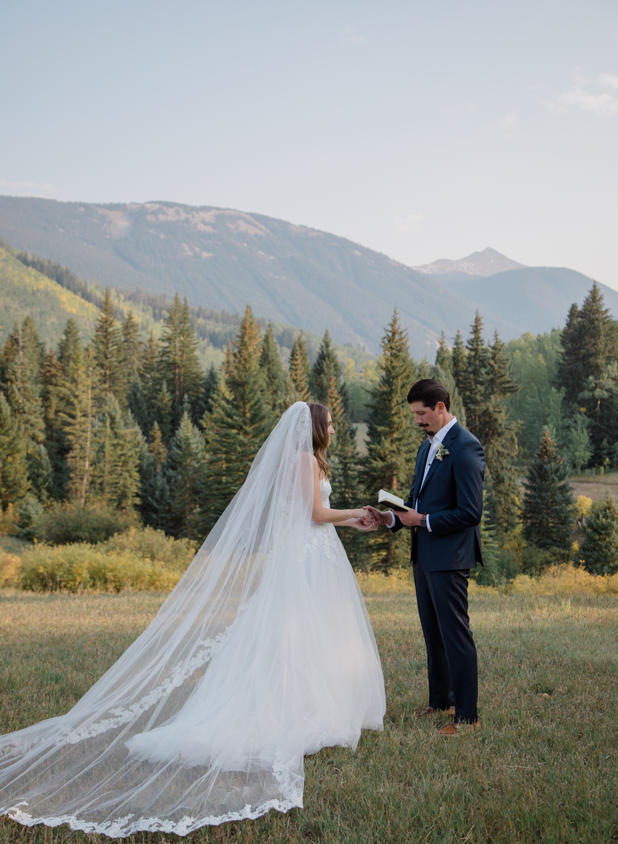 Bride and groom exchanging vows in mountains