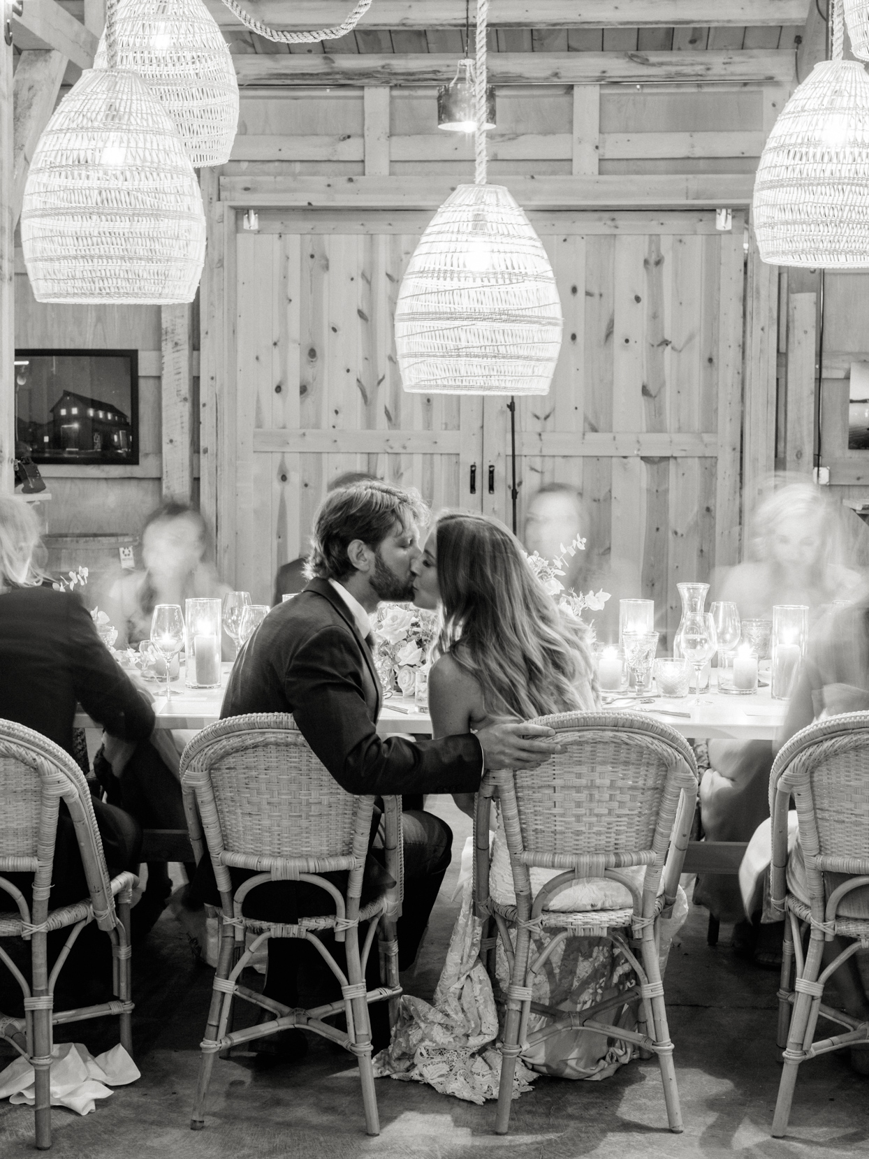 bride and groom kiss at table