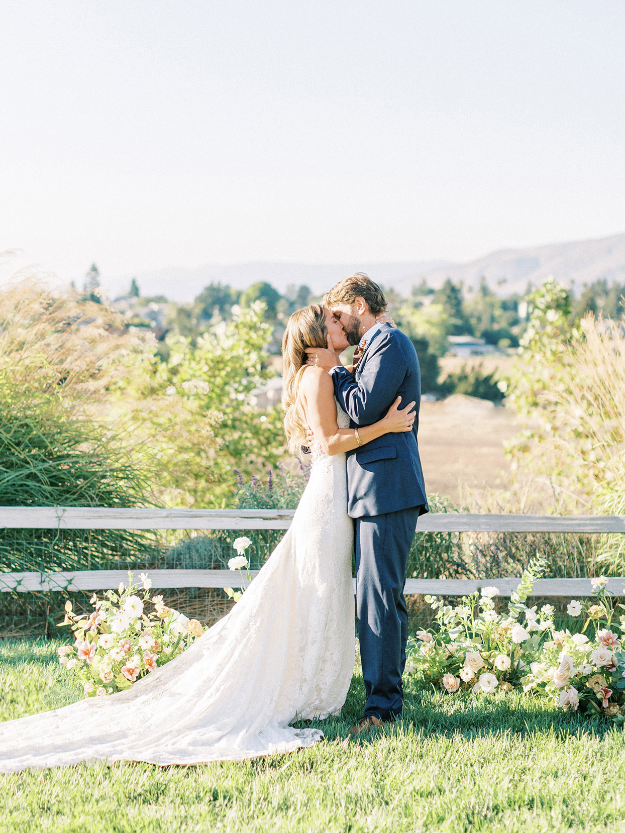bride and groom kiss near flowers