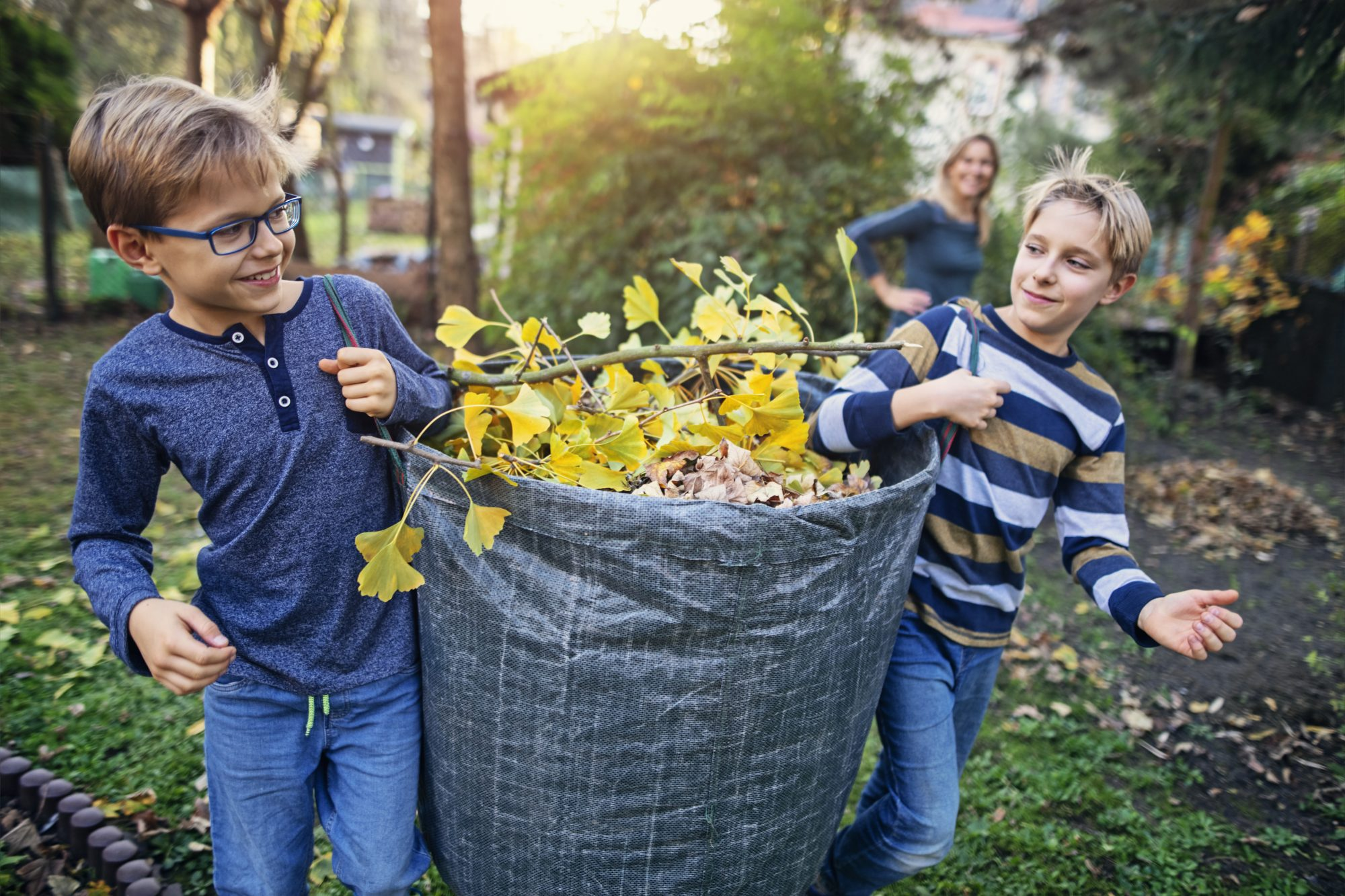 two boys carrying reusable bag full of leaves