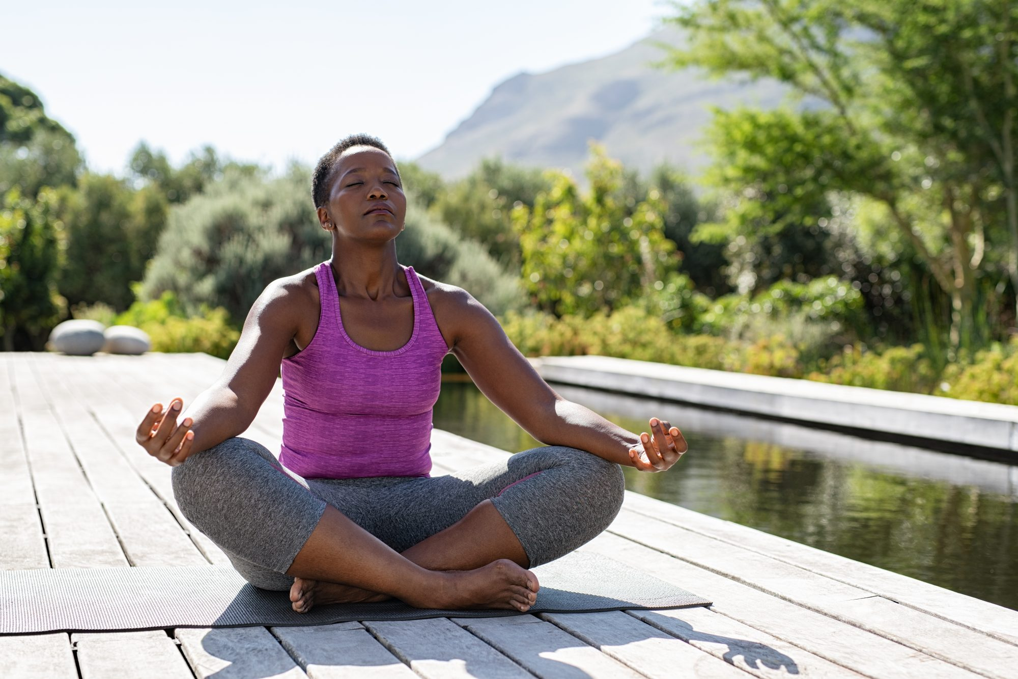 woman practicing yoga outdoors on deck