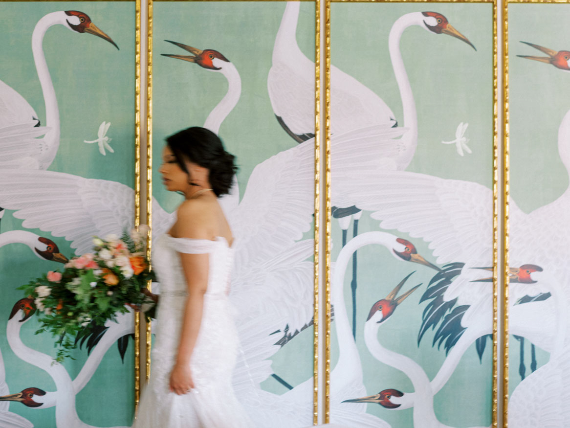 bride walking past painted wall with gold accents