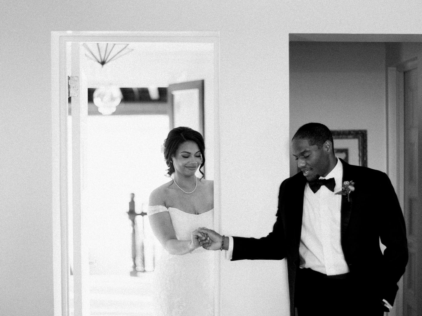 bride and groom first touch separated by doorway