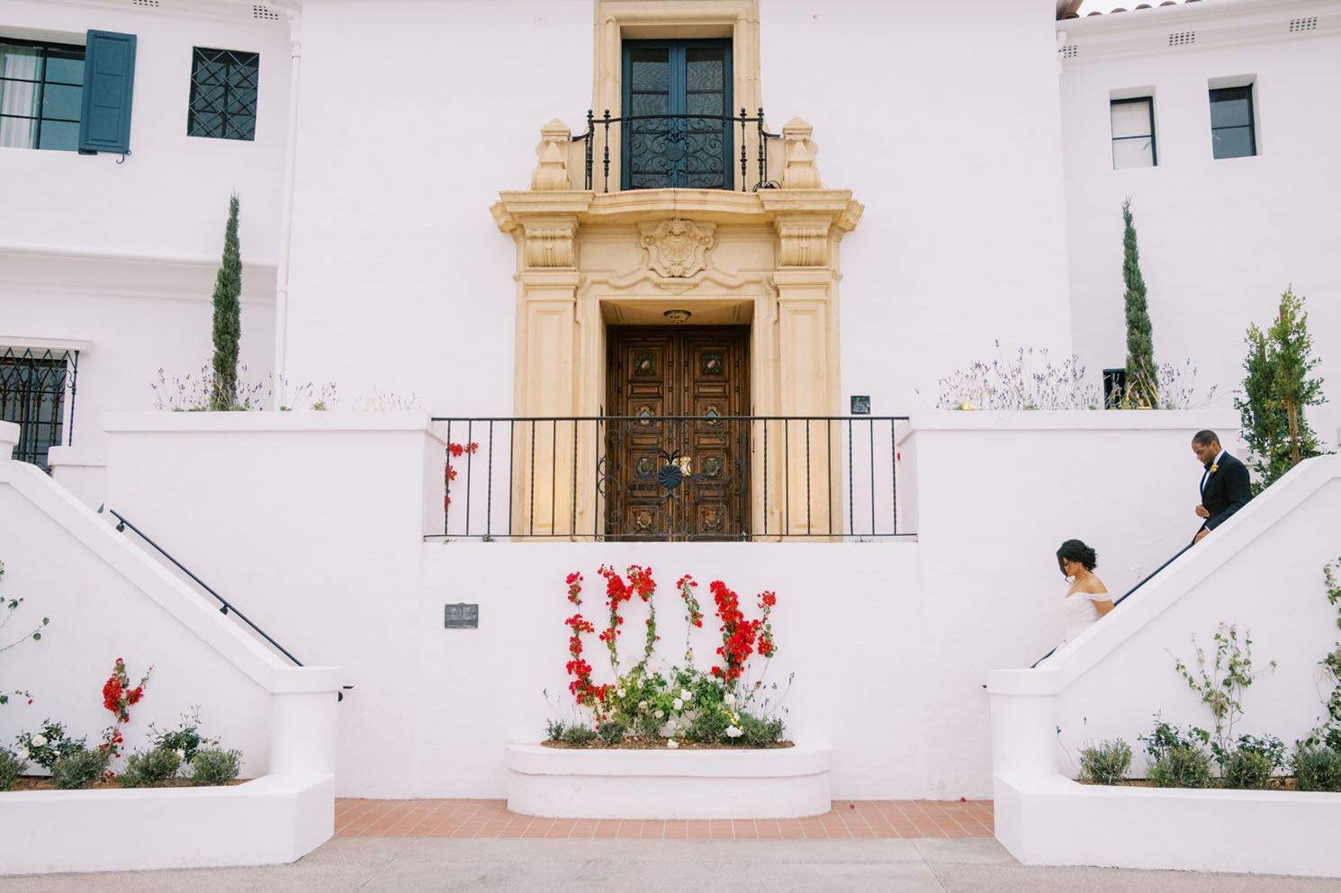 bride and groom descending stairs outdoors at venue
