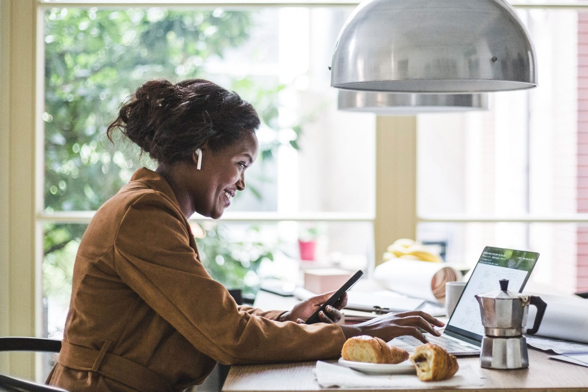 woman smiling working from home wearing earbuds