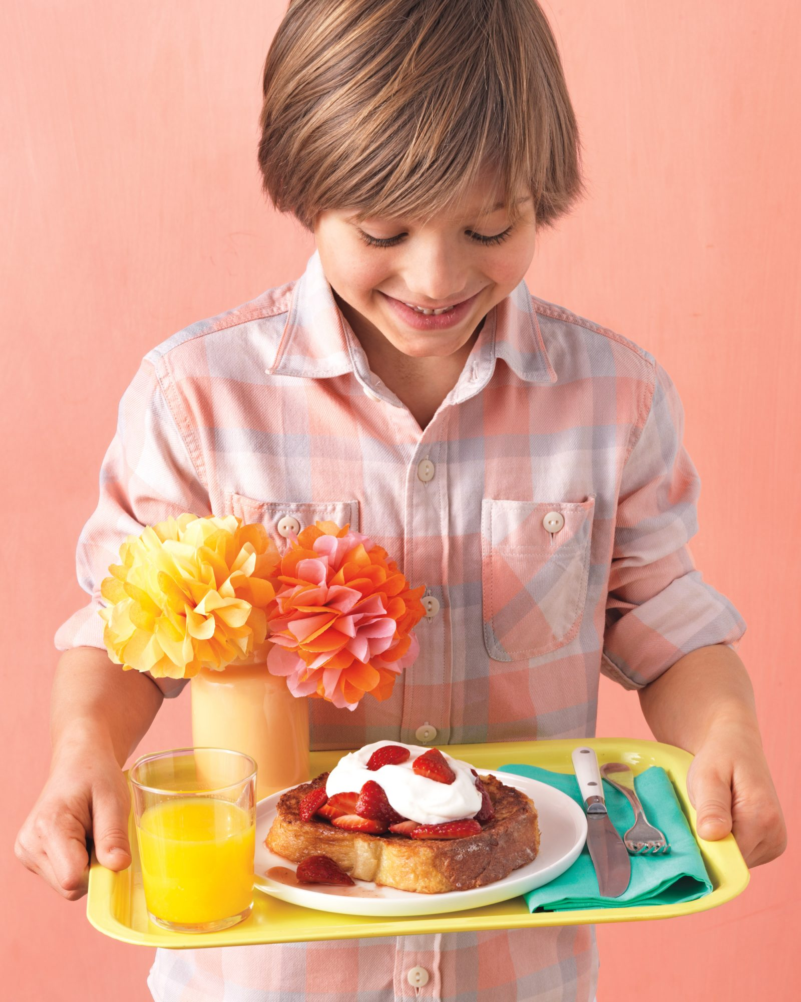 little boy holding a tray for breakfast in bed with paper flowers