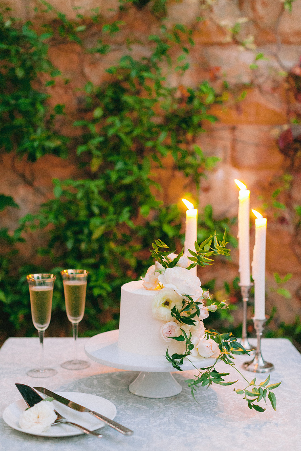 small wedding cake with florals and candles