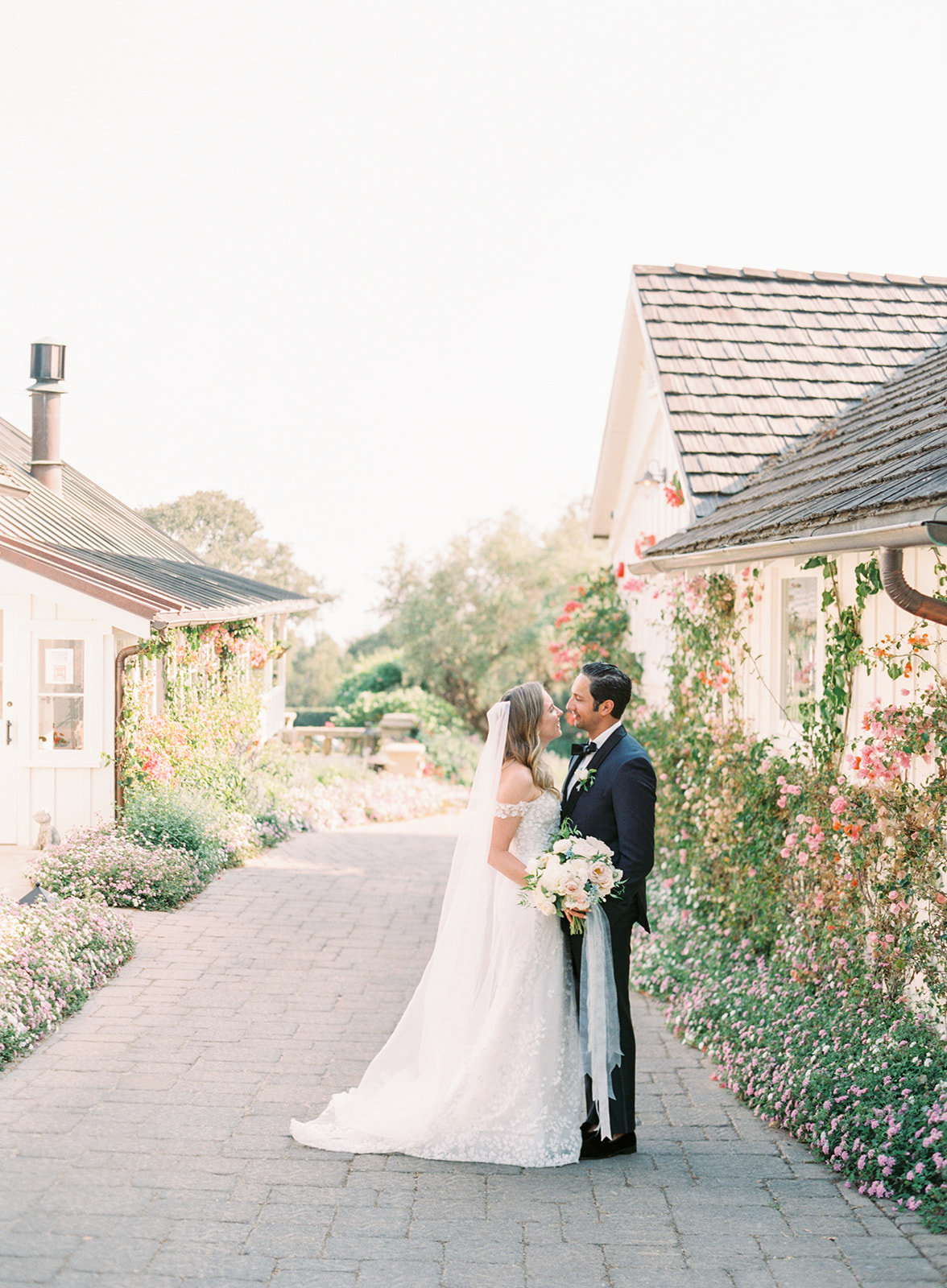 wedding portrait kiss on stone street with floral walled houses