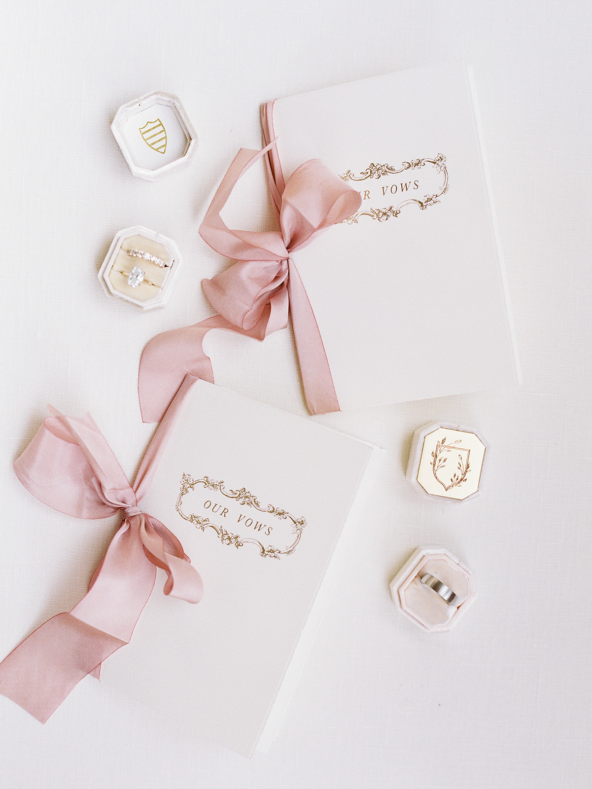 white vow books with pink bows tied on the side