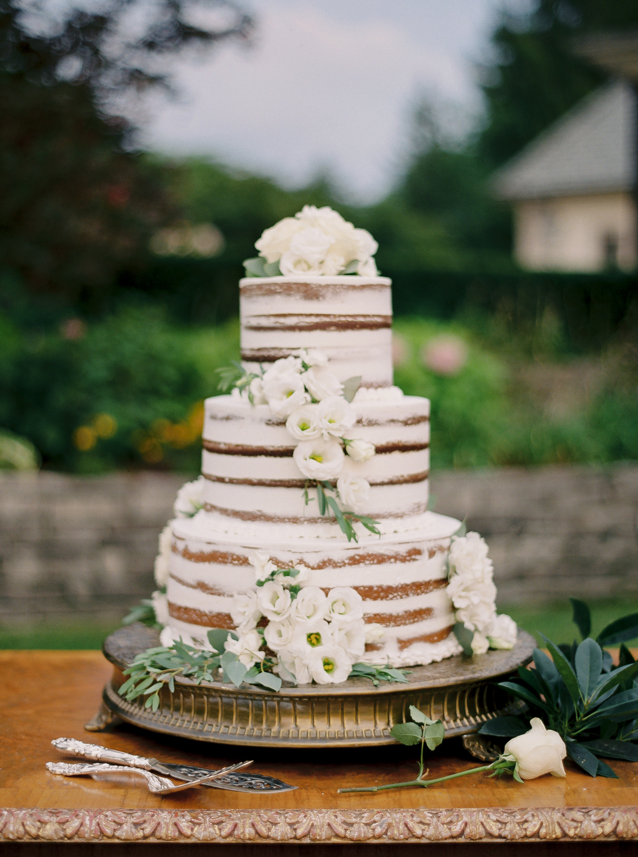 three-tiered wedding cake embellished with white flowers