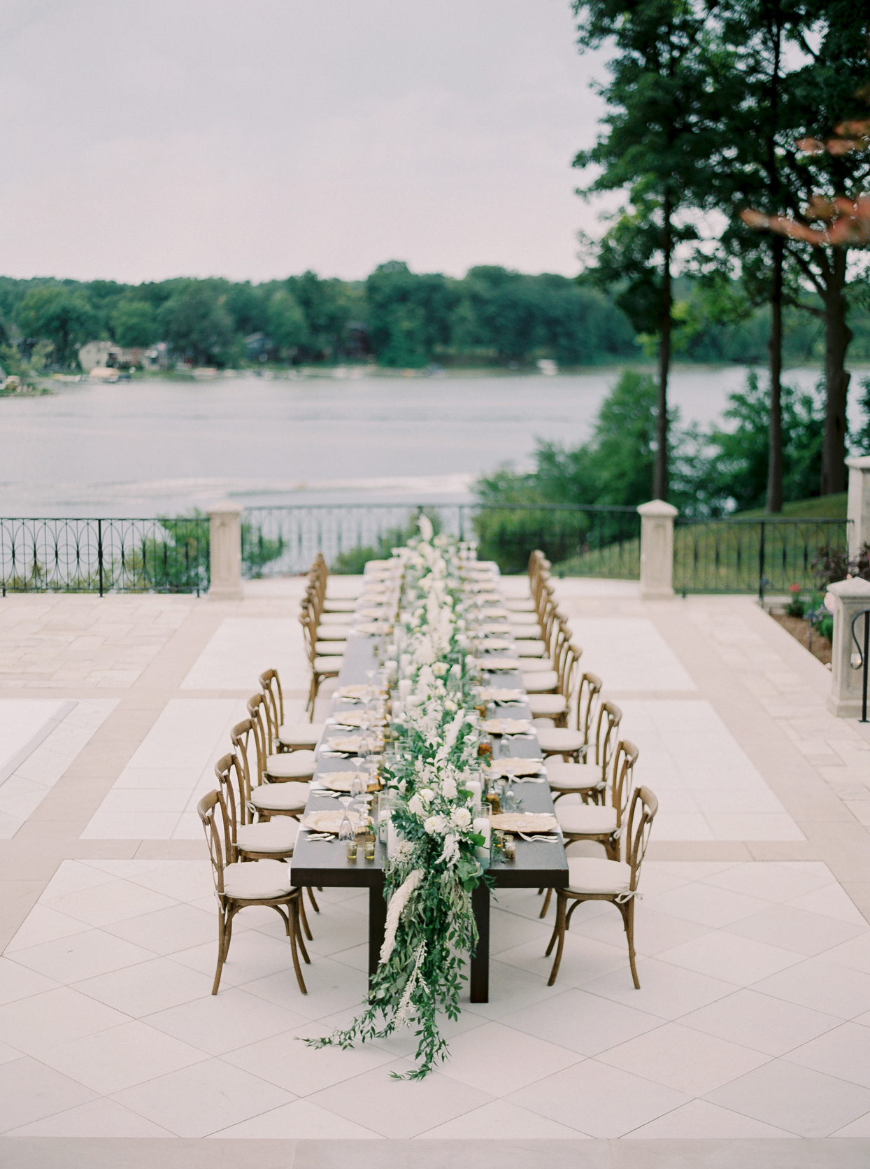 outdoor wooden wedding reception table with greenery and white flowers