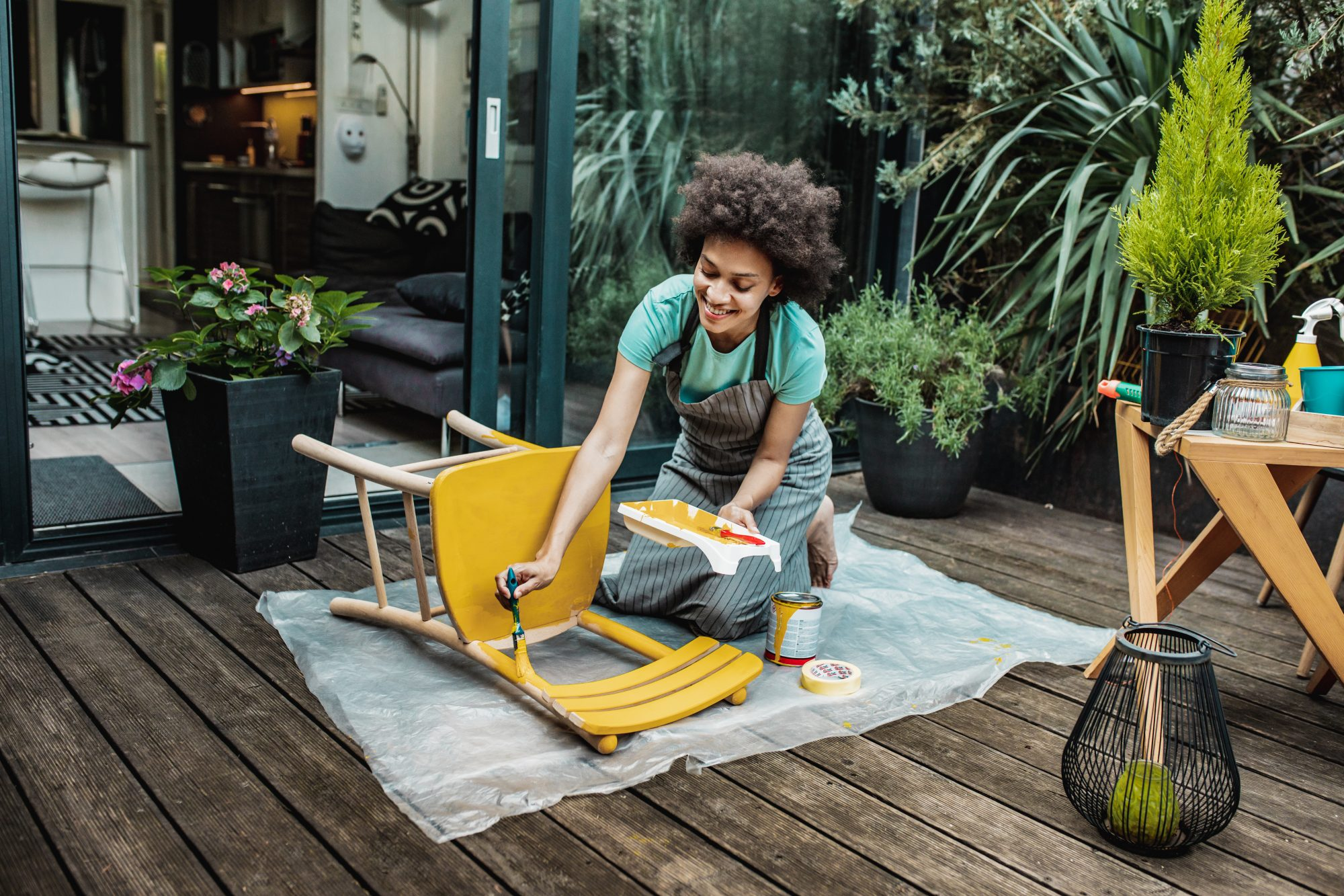 woman painting chair yellow outside on patio