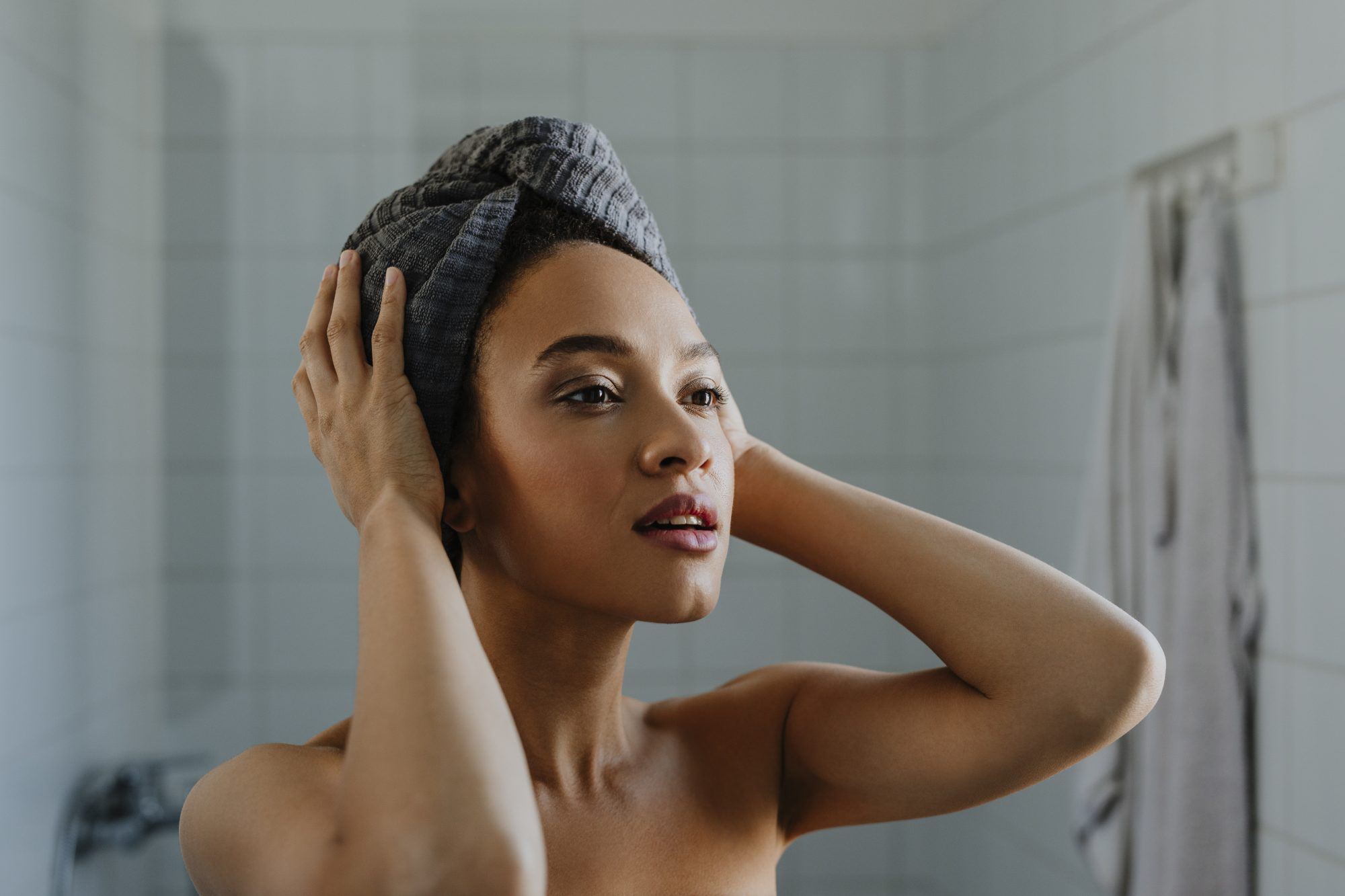 woman drying hair with towel after shower