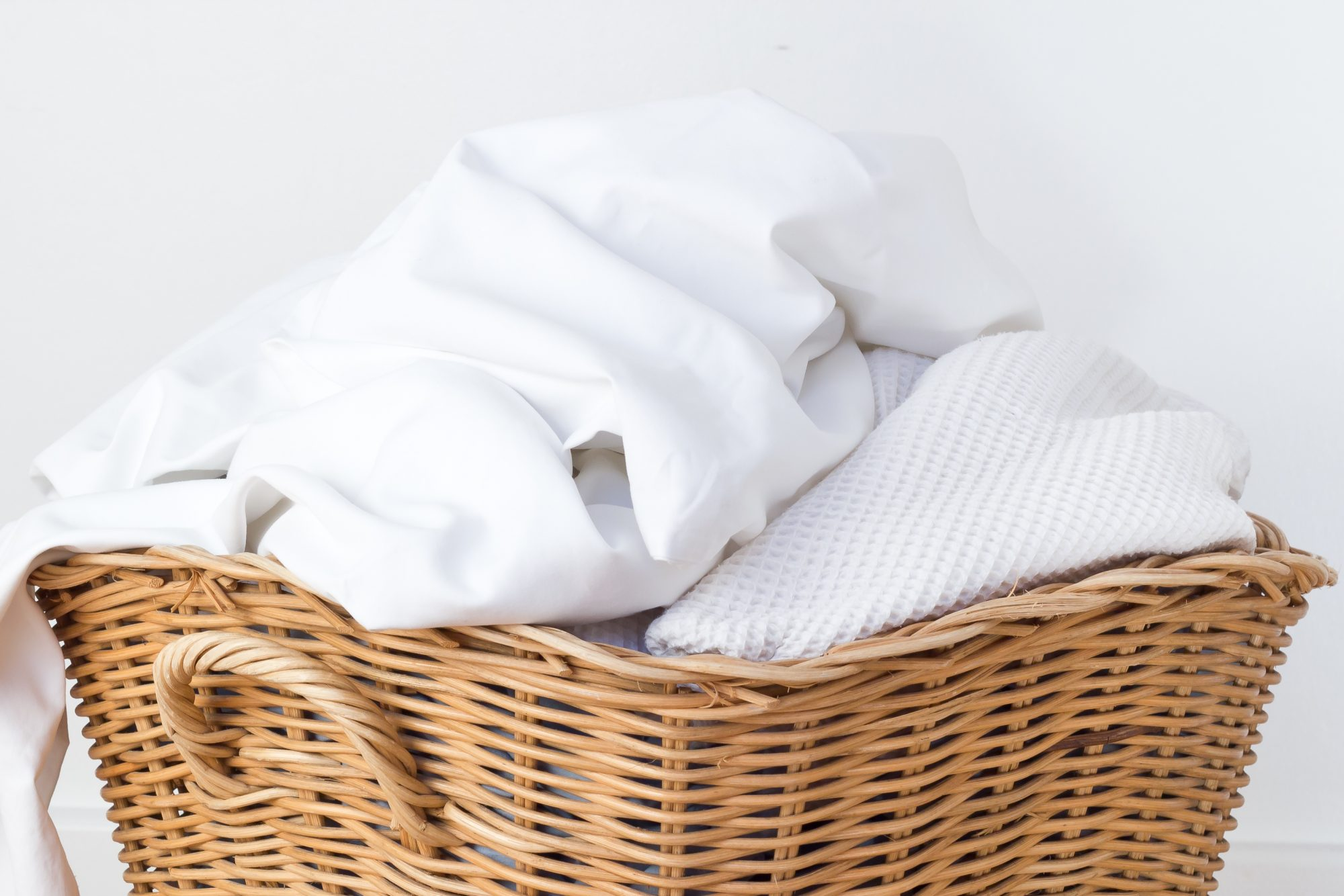 clean white sheets and towels in basket