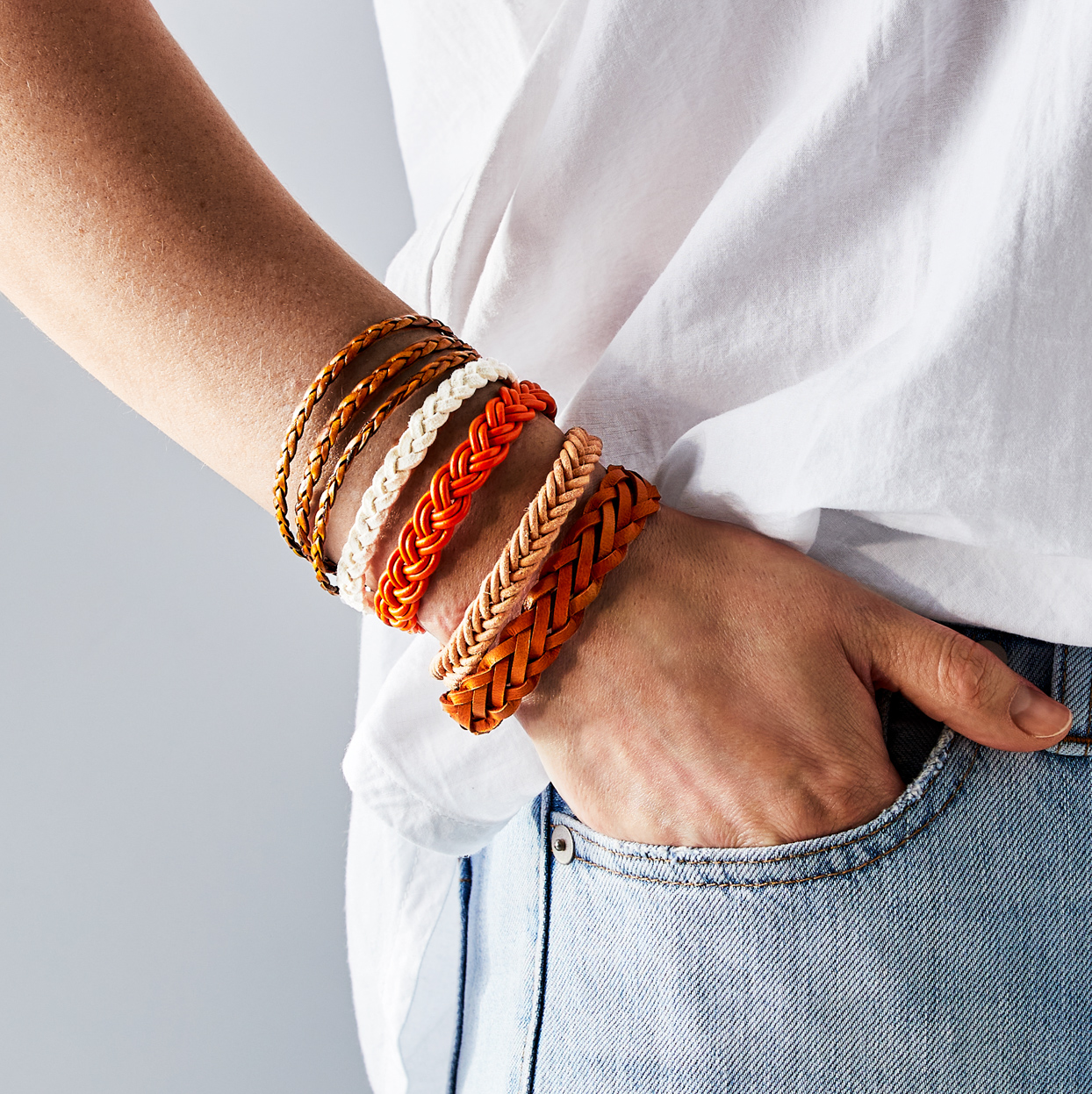 person wearing multiple braided leather bracelets