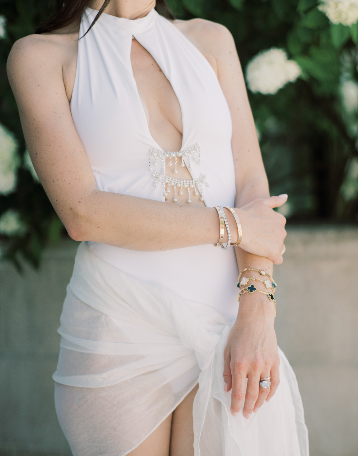 bride wearing jeweled white swimsuit with gold jewelry