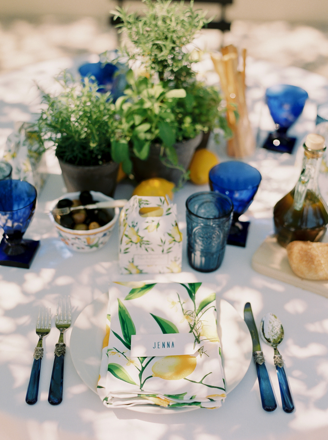 guest table setting with blue silverware and lemon printed napkins