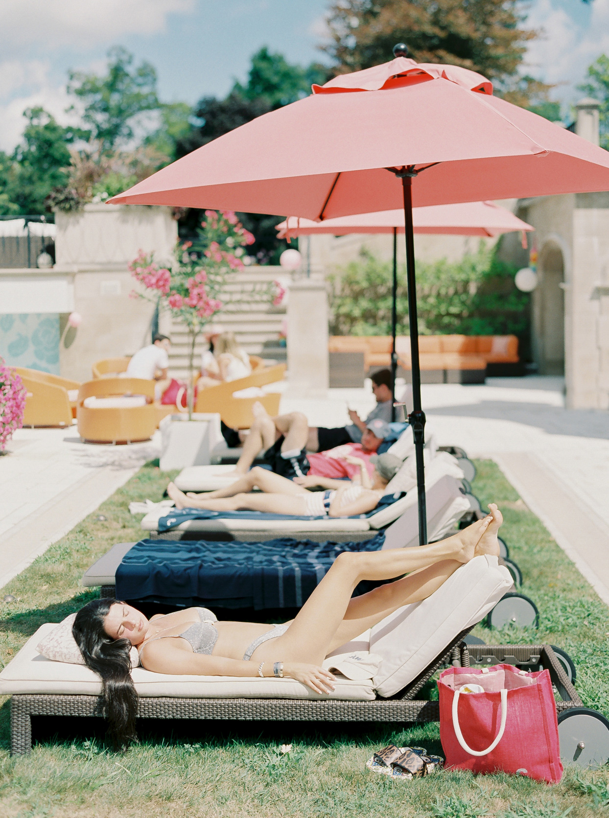 wedding guests lounging on pool chairs