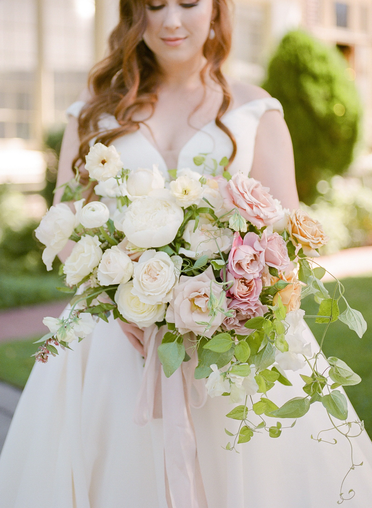 bride holding large white and blush toned rose bouquet