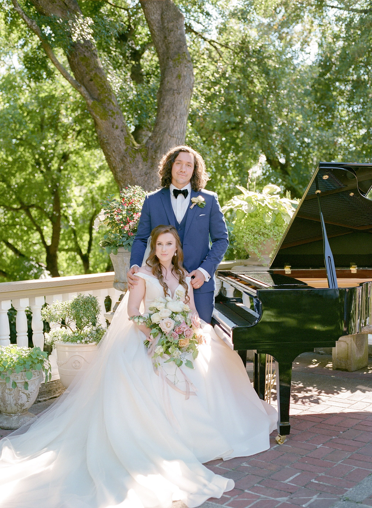 bride and groom posed next to grand piano outside