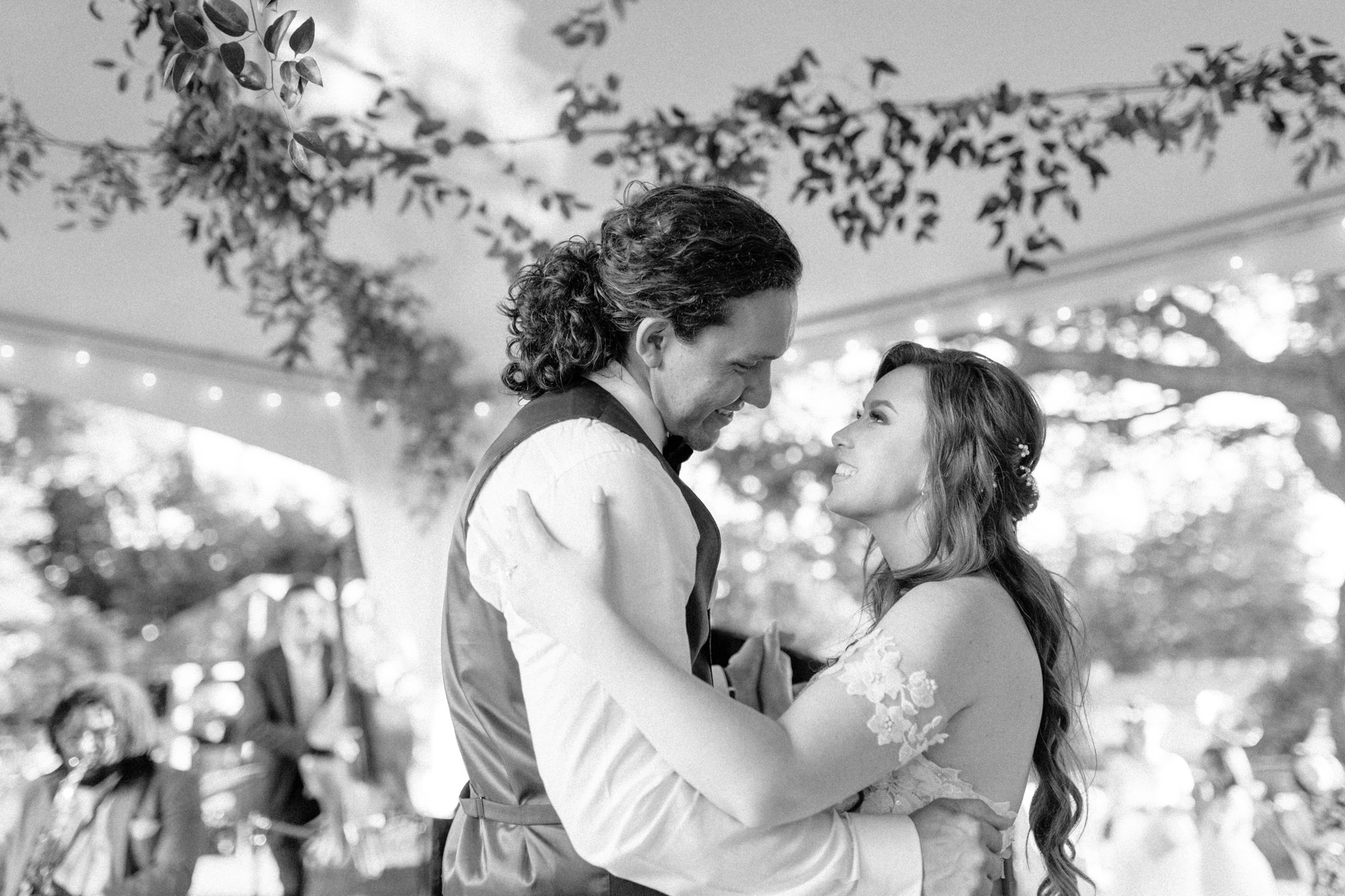 bride and groom smile while dancing