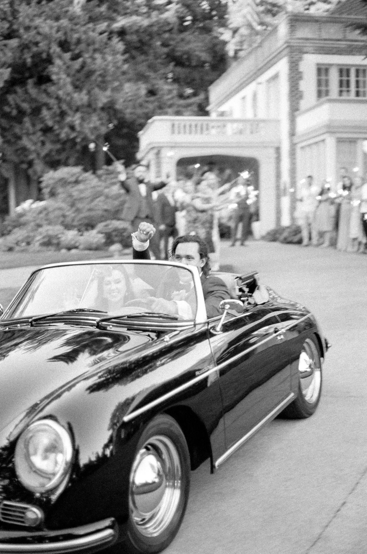 groom raises fist smiling driving away with bride in vintage car