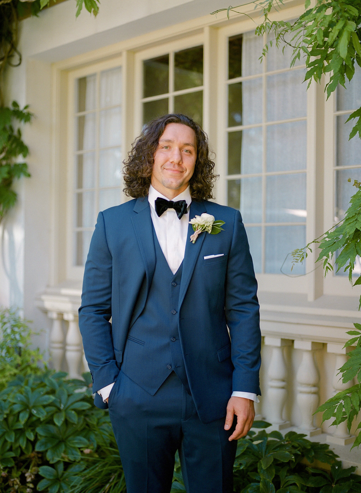 groom smiling wearing navy blue suit with white floral boutonniere