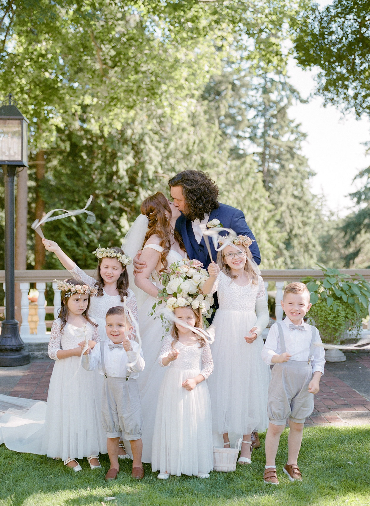 bride and groom share a kiss surrounded by nieces and nephews