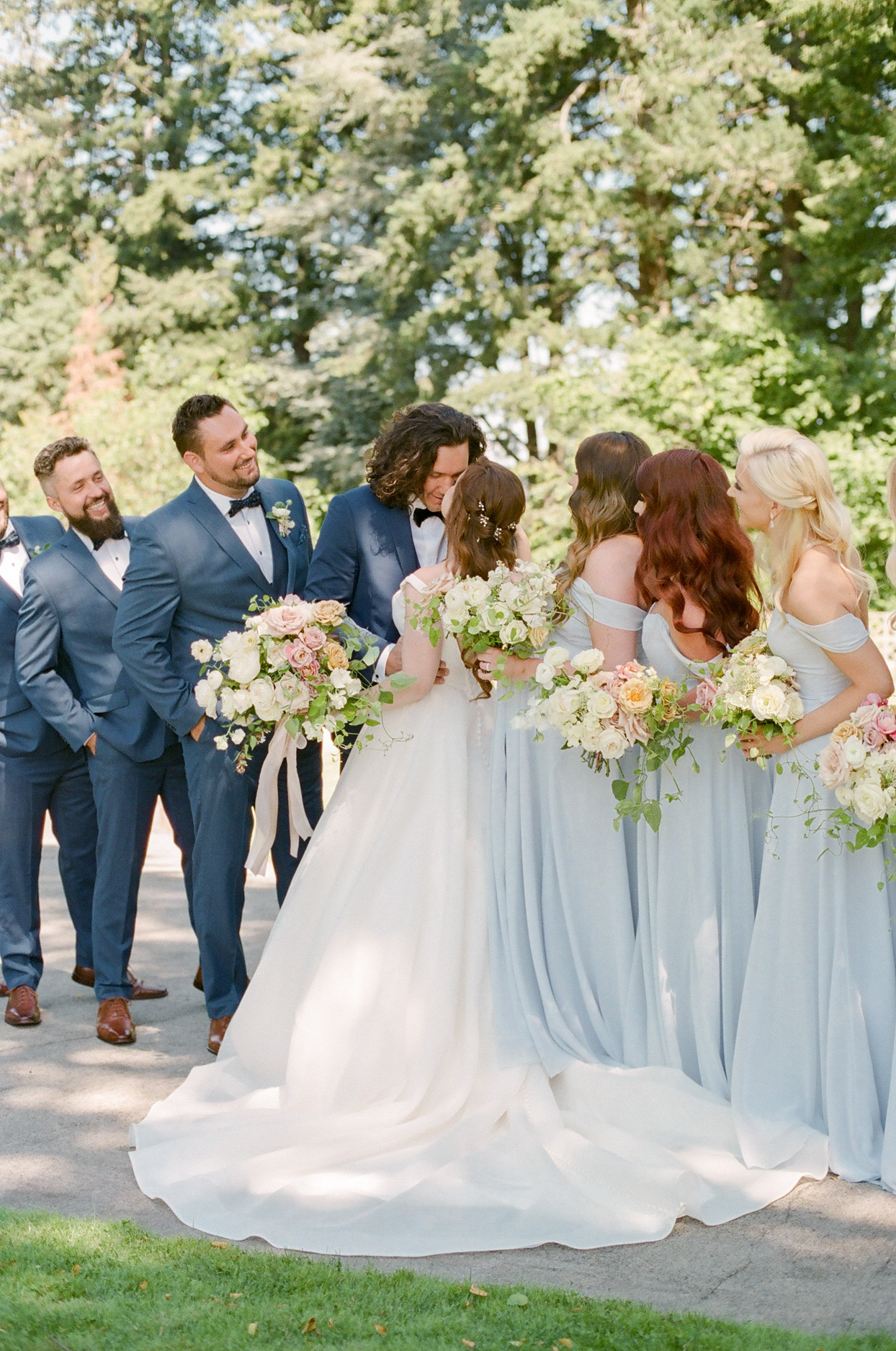 bride and groom share a kiss surrounded by wedding party