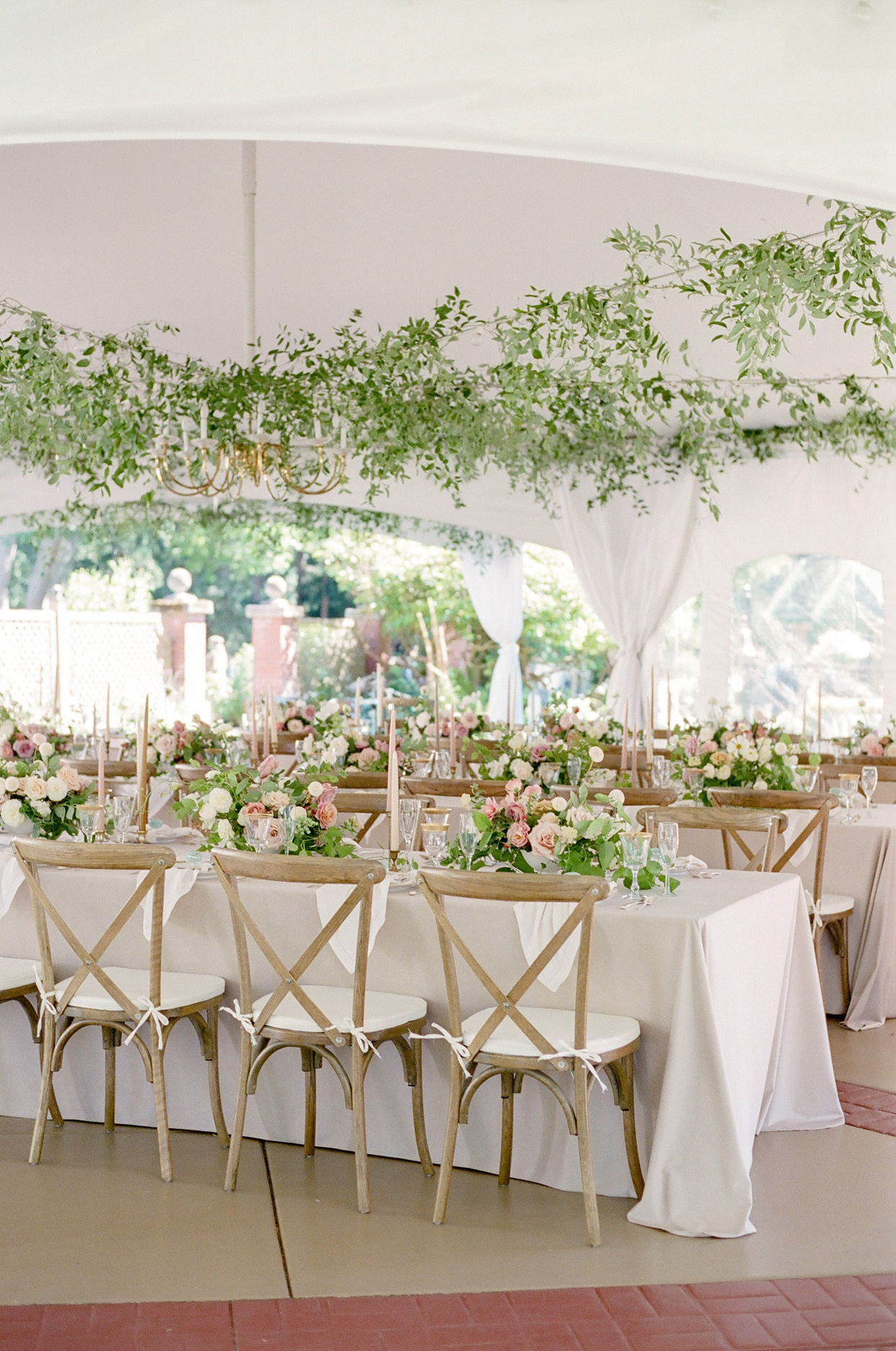 white reception tent covered long white linen draped tables with tapper candles