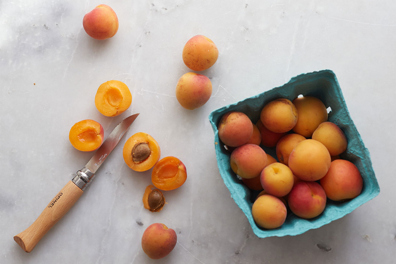 halved apricots on marble surface