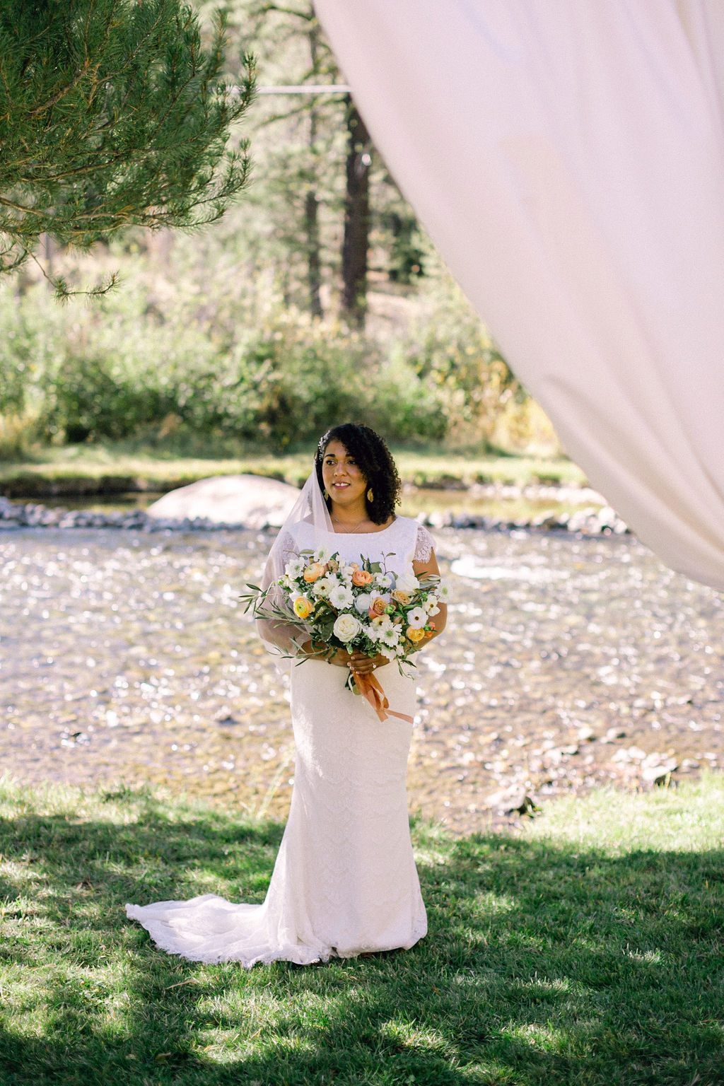 bride in lace cap sleeve wedding dress holding bouquet