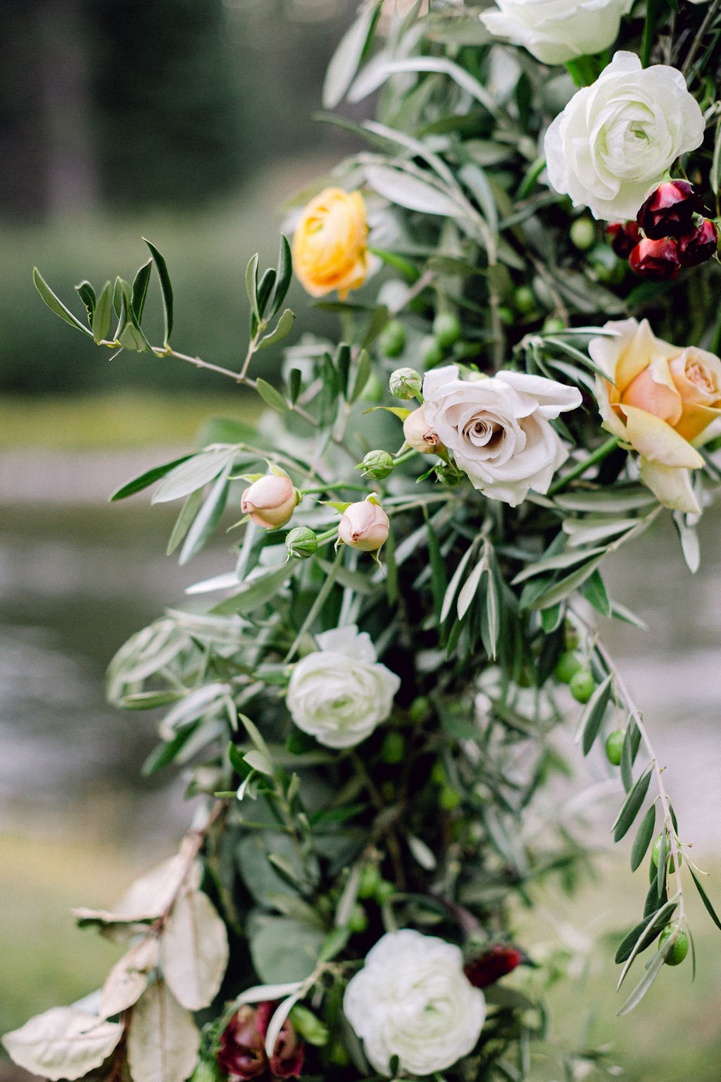 greenery covered wedding ceremony arch with floral accents