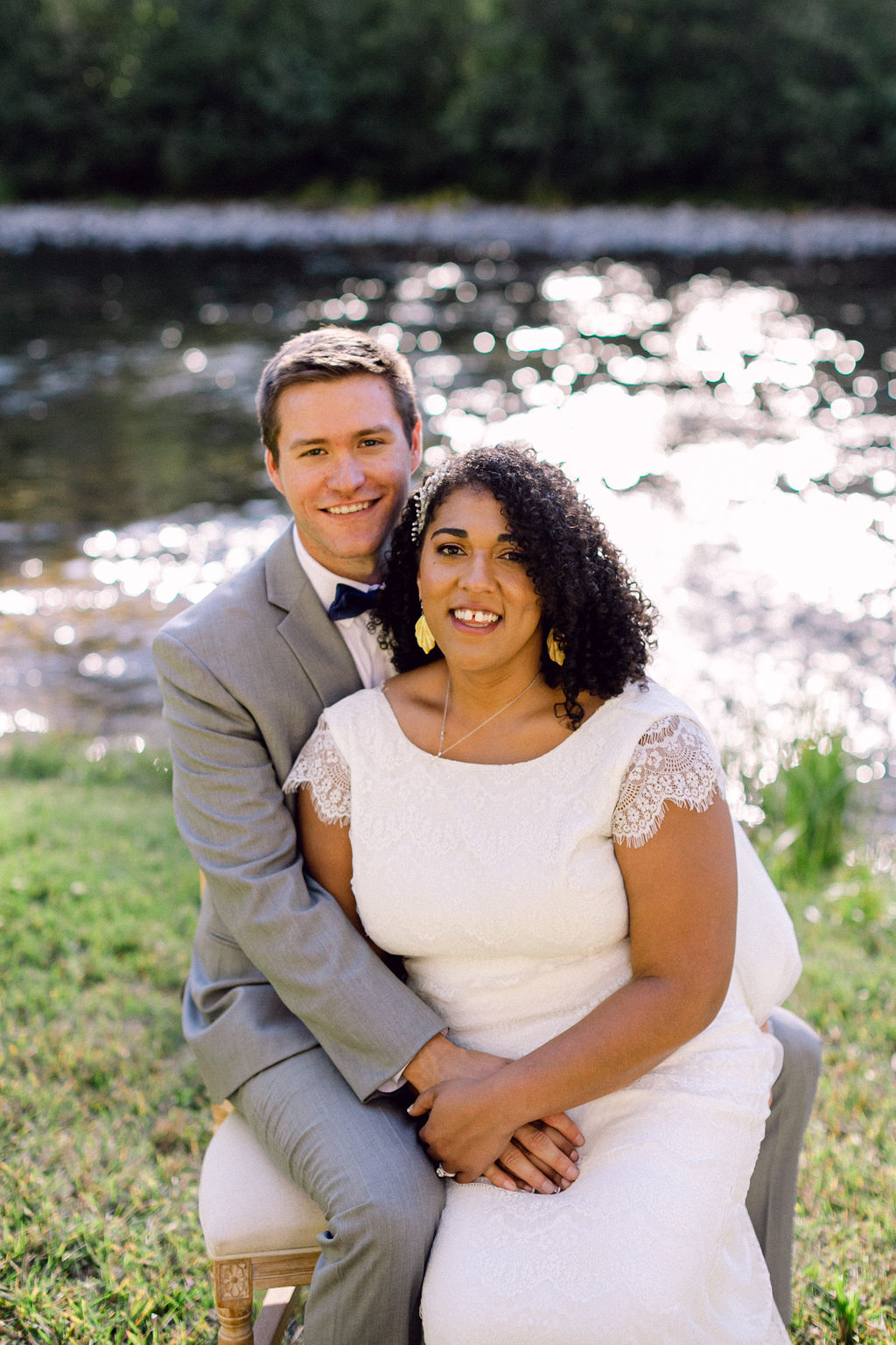 bride and groom sitting on chair outside smiling