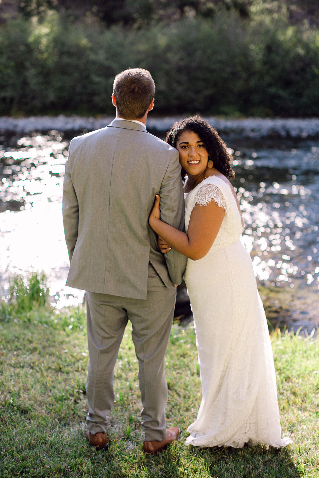 groom facing water while bride smiles holding his arm