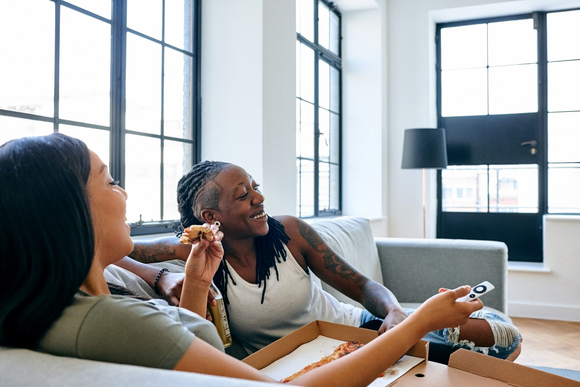 two woman watching movie on couch eating pizza