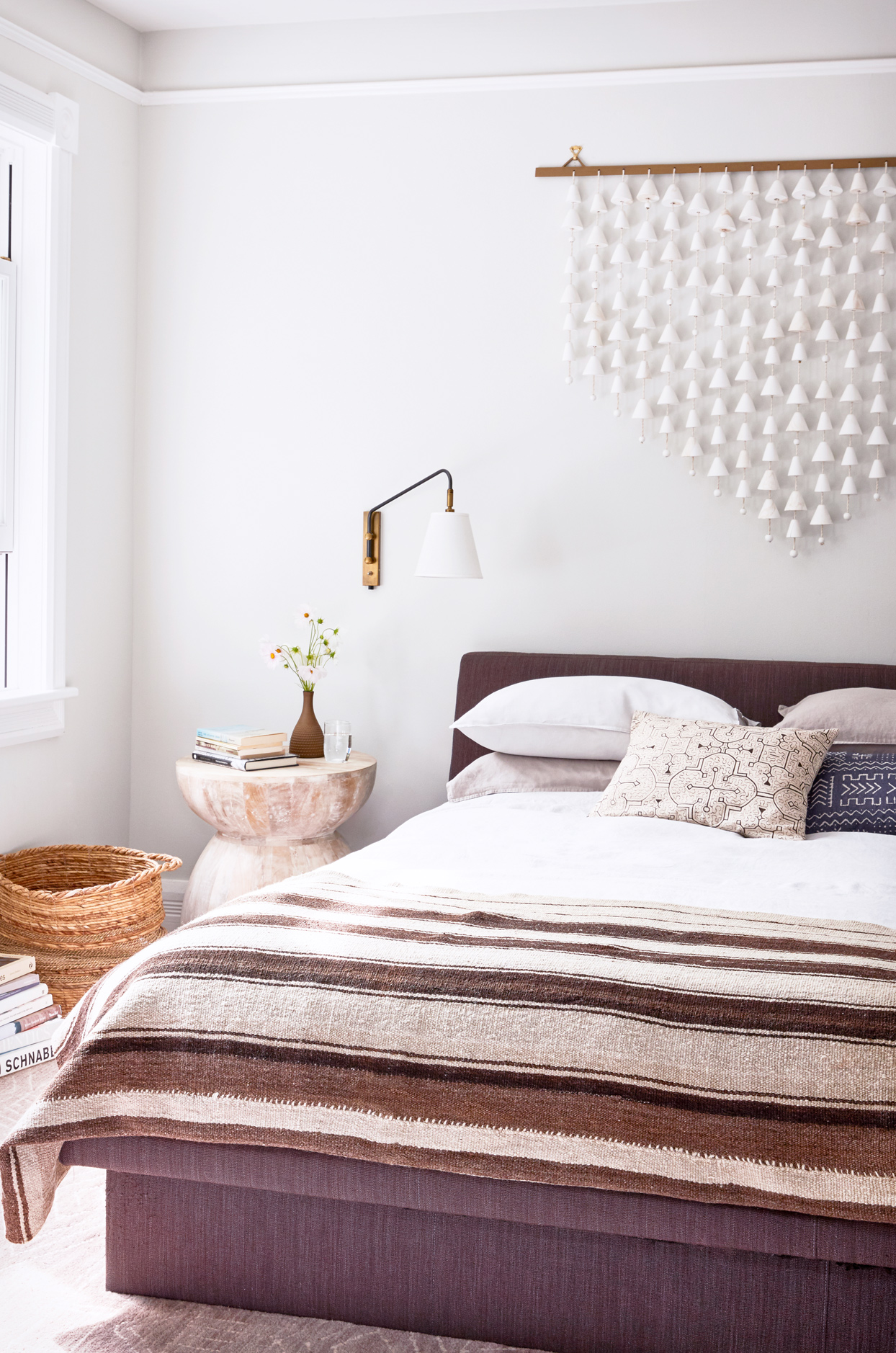 boho master bedroom with wall hanging and hand-loomed coverlet