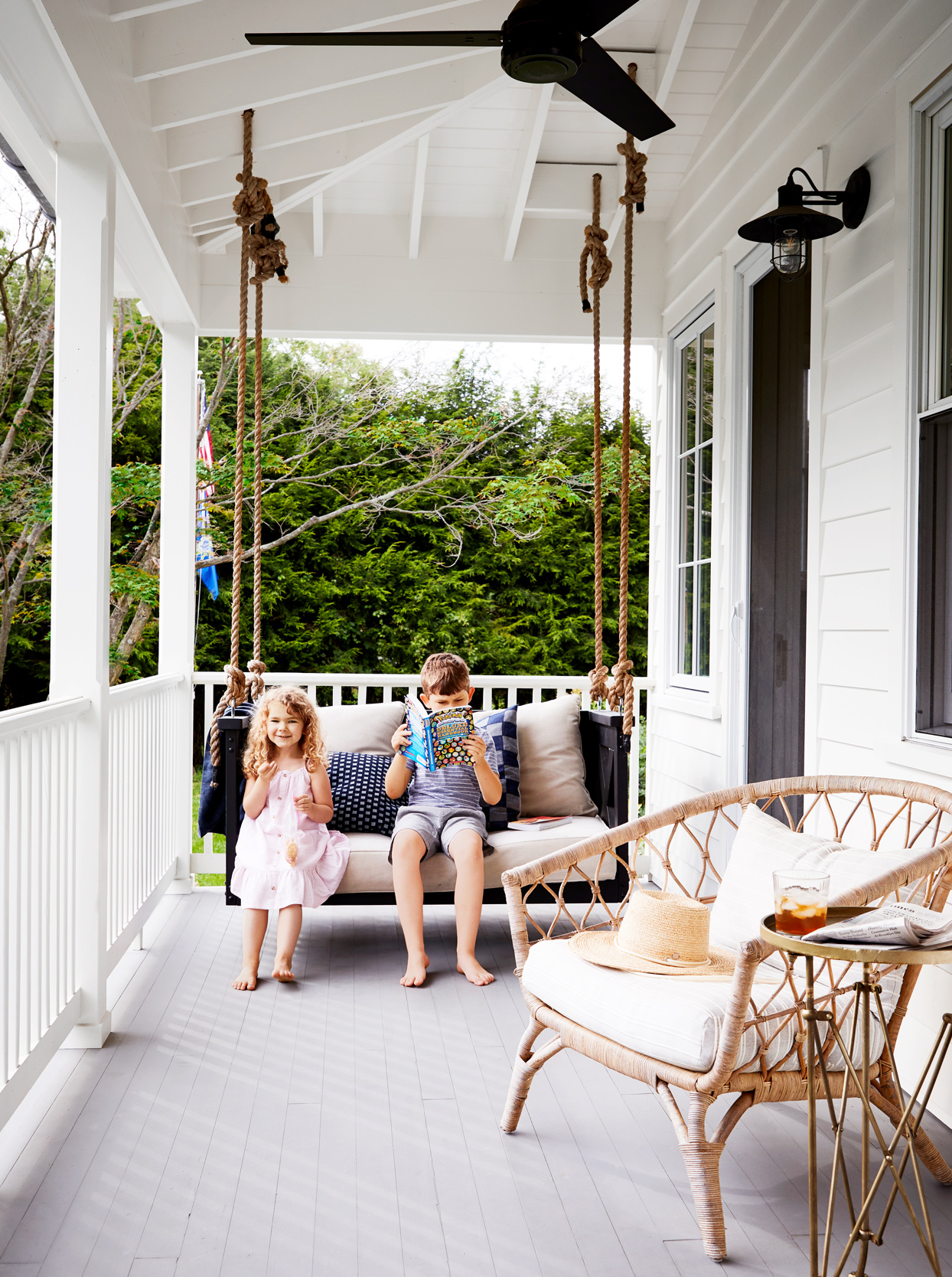 children sitting on front porch swing bed