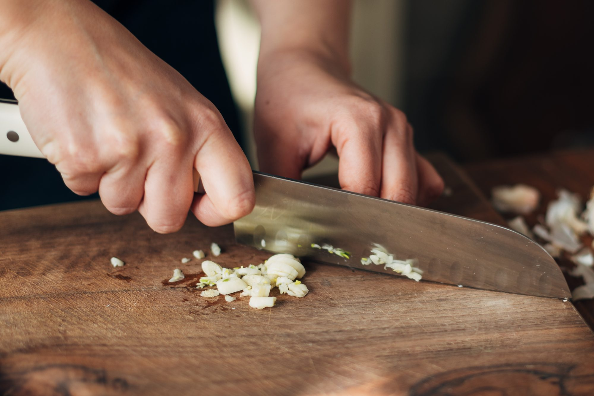 chopping garlic on wood cutting board