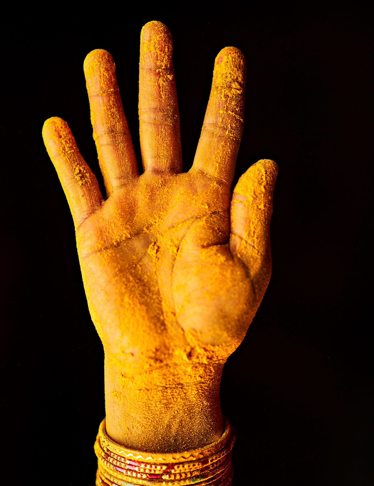 hand covered in turmeric powder