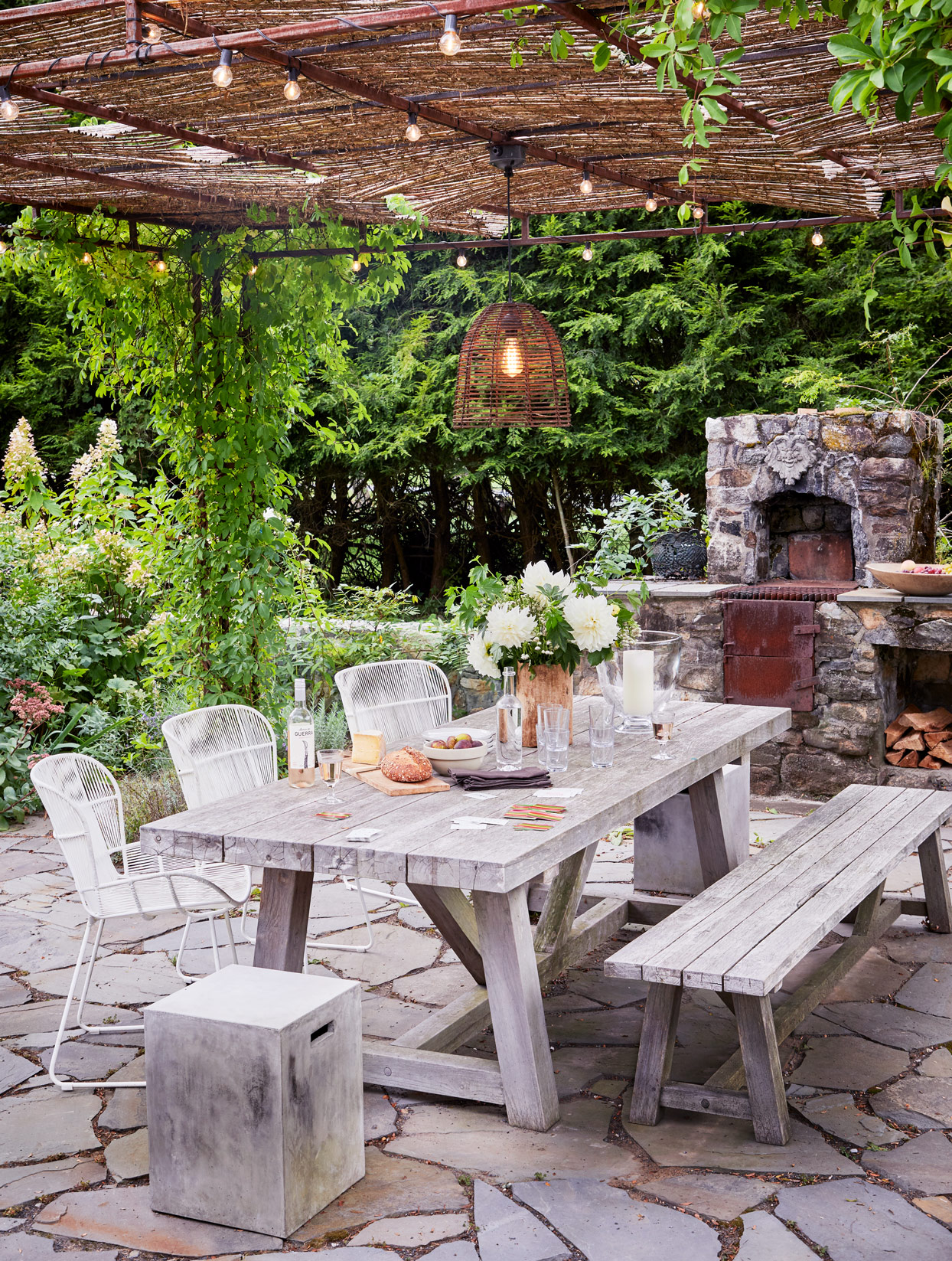 homes side terrace with wooden table and stone fireplace