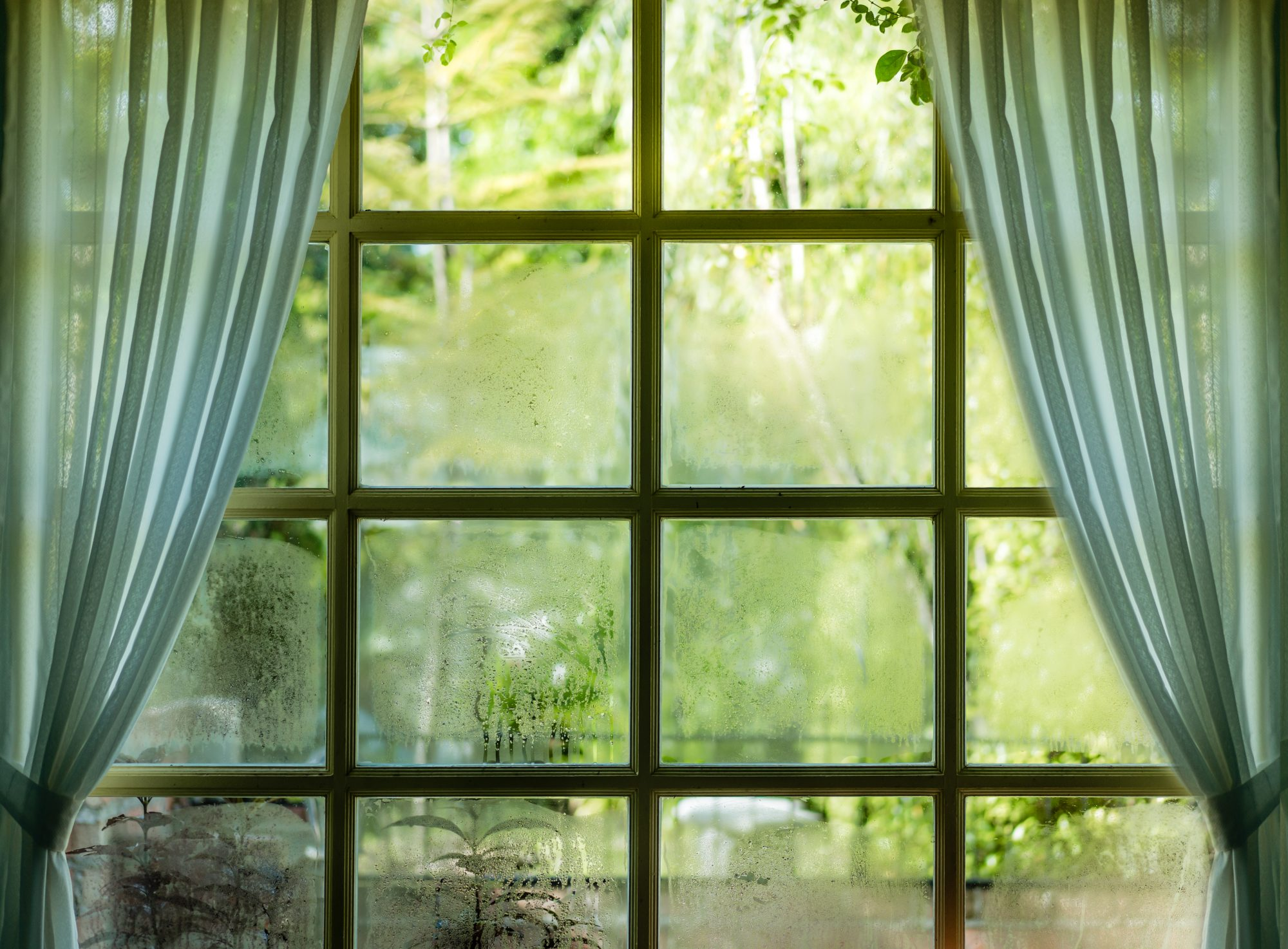 Glass window with condensation and curtains