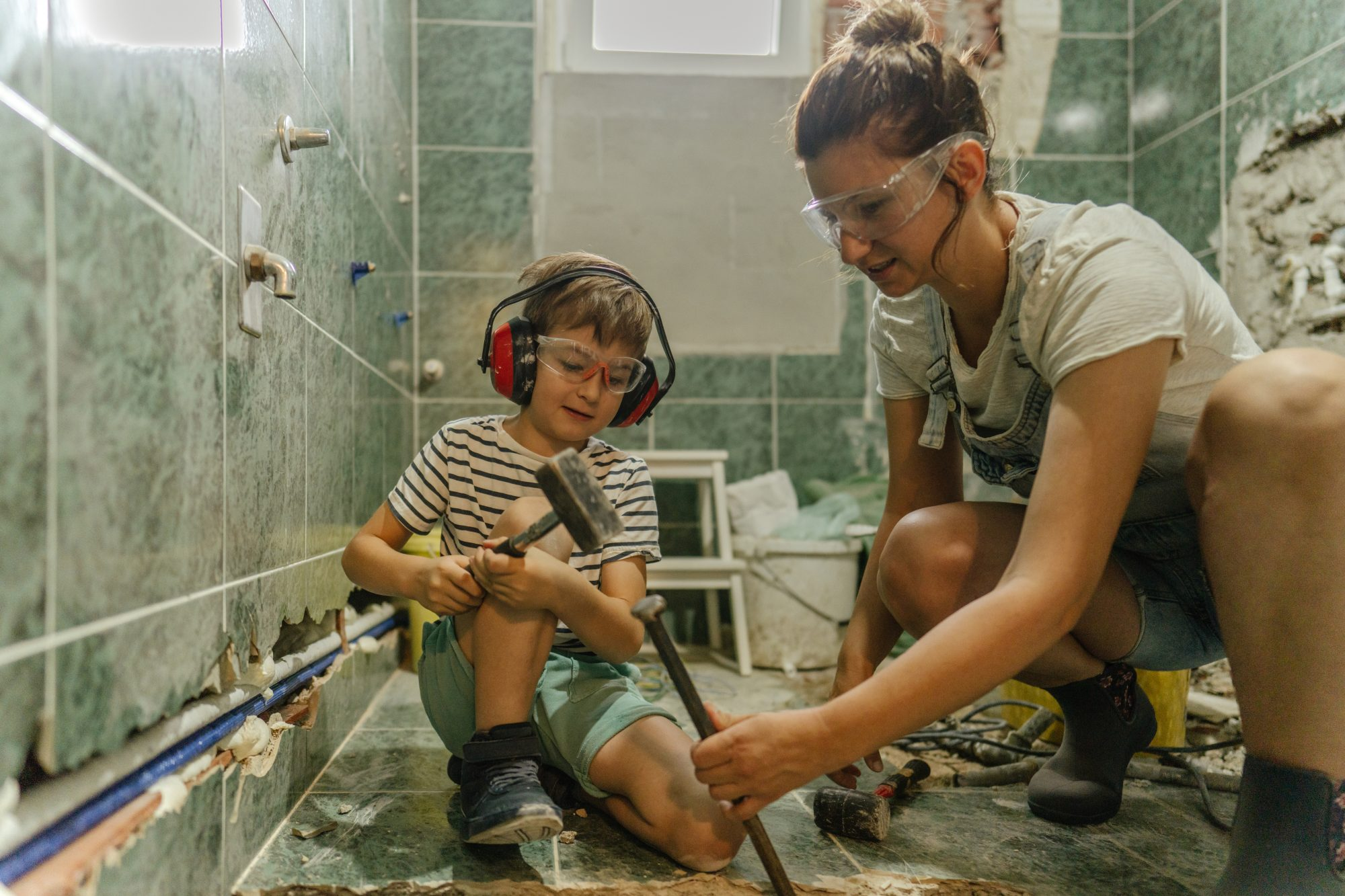 mother and son renovating bathroom tile
