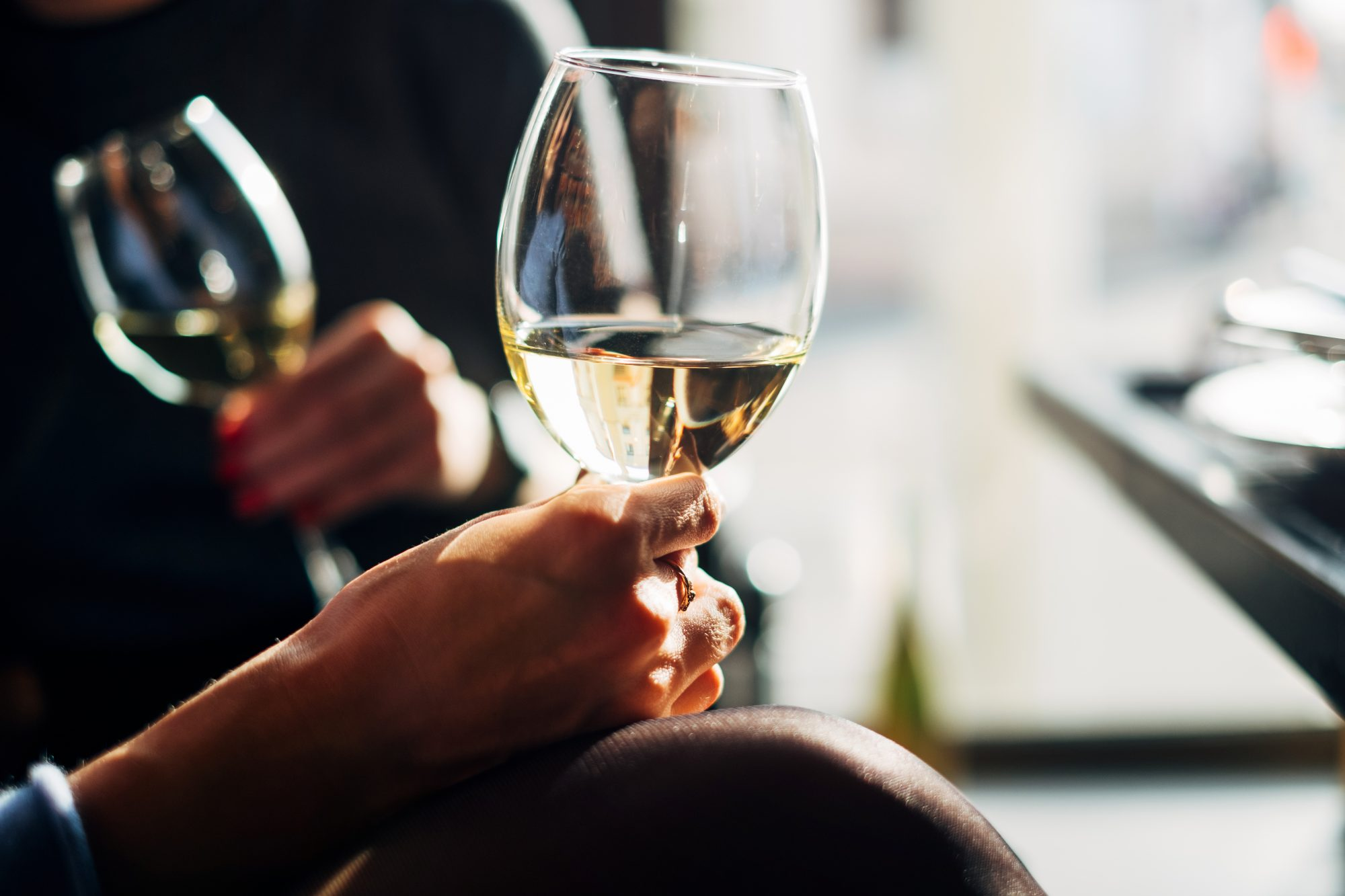 woman sitting at table drinking white wine